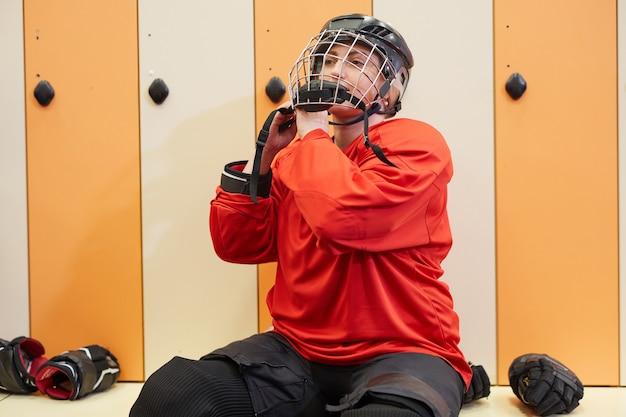 Porträt der hockeyspielerin, die helm im umkleideraum aufsetzt