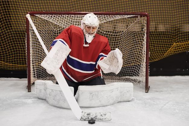 Porträt der hockeyspielerin in voller länge, die das tor in voller ausrüstung verteidigt