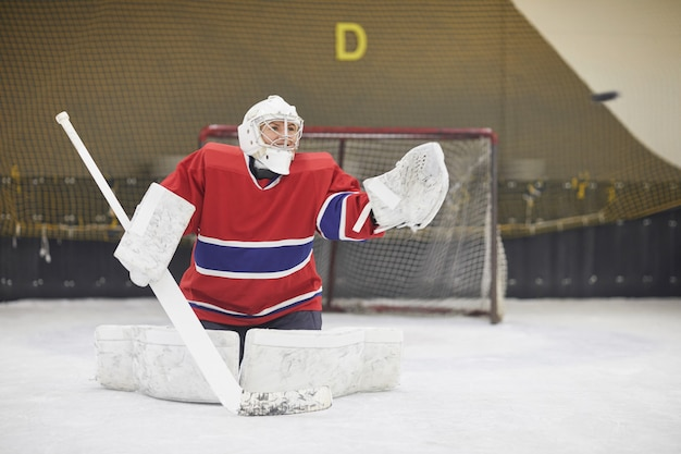 Porträt der hockeyspielerin in voller länge in voller ausrüstung