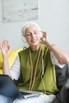 Porträt der hörenden musik der älteren frau auf kopfhörer