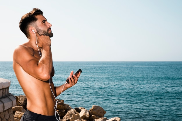 Porträt der hörenden musik des sportiven mannes