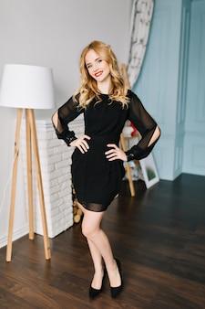 Porträt der hübschen blonden dame in voller länge, die elegantes schwarzes kleid und schuhe im modernen raum, hellen raum mit falschem kamin, weiße stehlampe trägt. sie hat ein schönes lächeln und langes, welliges haar.