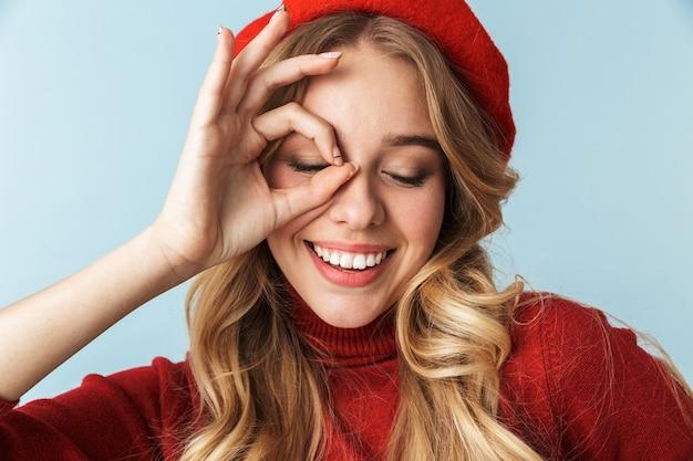 Porträt der hübschen blonden frau 20s, die rote baskenmütze zeigt, die ok zeichen im stehen zeigt, isoliert
