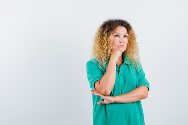 Porträt der hübschen blonden frau, die kinn auf hand im grünen polo-t-shirt stützt und nachdenkliche vorderansicht schaut