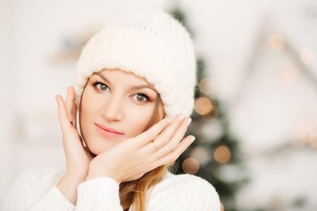 Porträt der hübschen blonden frau in der weißen wintermütze, die hände im gesicht gegen bokeh-effekt mit silhouette des weihnachtsbaumes hält