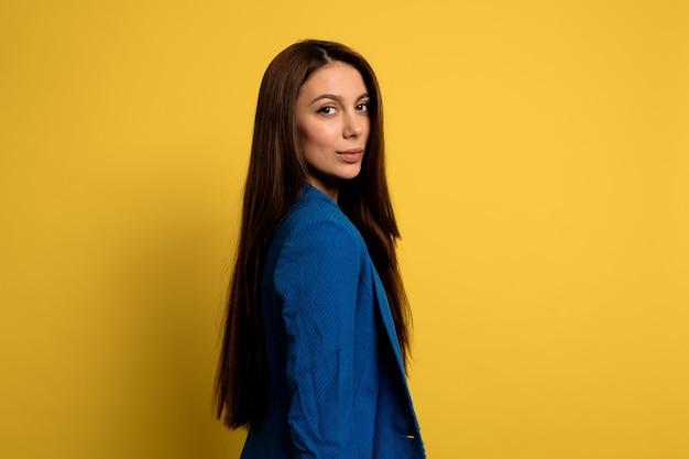 Porträt der hübschen charmanten dame mit dem langen dunklen haar, das blaue jacke über gelber wand trägt