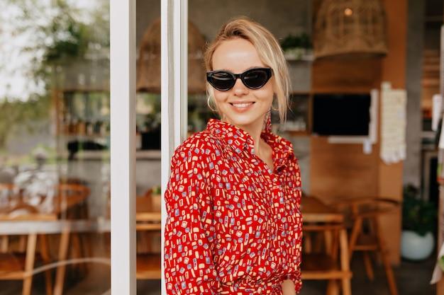 Porträt der hübschen charmanten frau mit dem blonden haar, das brille und helles kleid trägt und lächelt