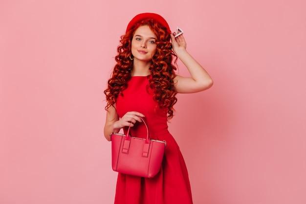 Porträt der hübschen dame mit gewellten roten haaren und blauen augen. mädchen im roten kleid zieht ihre baskenmütze an und hält ihre tasche.