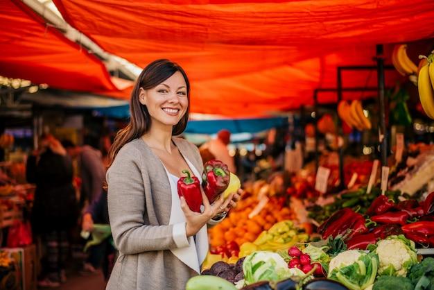 Porträt der hübschen frau am kaufenden paprika des landwirtmarktes.