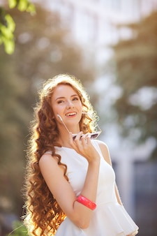 Porträt der hübschen frau der mode, die eine elegante retro-sonnenbrille trägt, die in stadt geht und glücklich wegschaut.