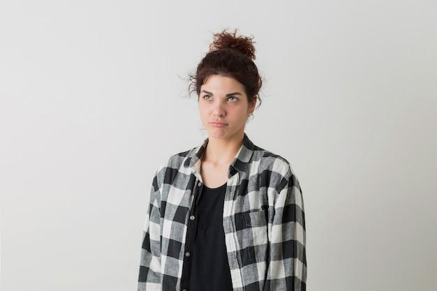 Porträt der hübschen frau des jungen hipsters im karierten hemd, das denkend ein problem hat und lokalisiert auf weißem studiohintergrund aufwirft