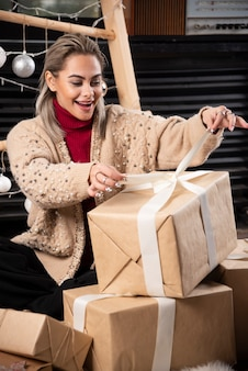 Porträt der hübschen frau, die eine schachtel des weihnachtsgeschenks öffnet