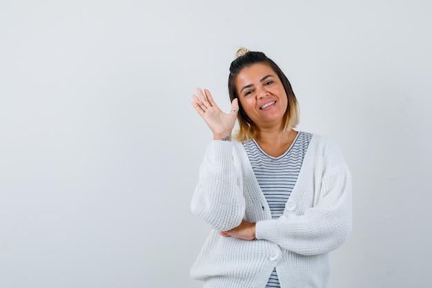 Porträt der hübschen frau, die hand zum gruß im t-shirt, in der strickjacke und in der fröhlichen vorderansicht winkt