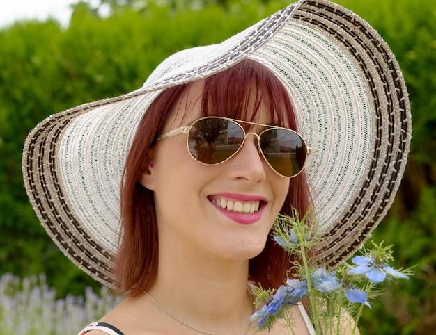 Porträt der hübschen frau, die hut und sonnenbrille trägt