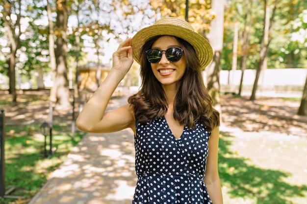 Porträt der hübschen frau, die in den grünen sommerpark geht, gekleidet in kleid und hut. hält ihren hut. sonniger sonnentag.