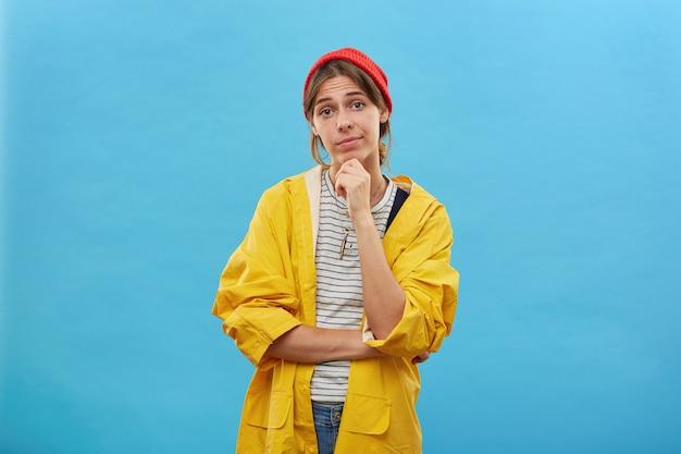 Porträt der hübschen frau gekleidet im gelben regenmantel und im roten hut, die ihre hand am kinn halten und direkt gehen, um im wald oder zum fluss isoliert zu gehen