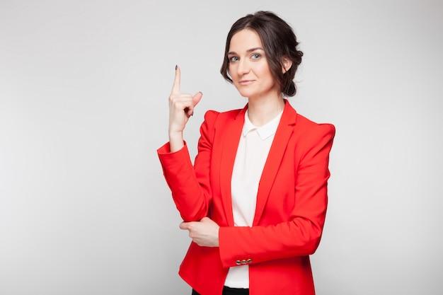 Porträt der hübschen frau im roten blazer, der zeichen zeigt