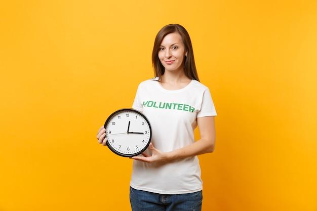 Porträt der hübschen frau im weißen t-shirt mit der schriftlichen aufschrift grünem titel freiwilliger halten die runde uhr einzeln auf gelbem hintergrund. freiwillige kostenlose hilfe, wohltätigkeitsarbeitszeitkonzept