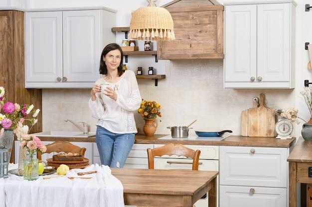 Porträt der hübschen frau in der freizeitkleidung in der küche mit tasse kaffee in der hand