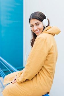 Porträt der hübschen frau in hörender musik der gelben jacke, die auf geländer sitzt