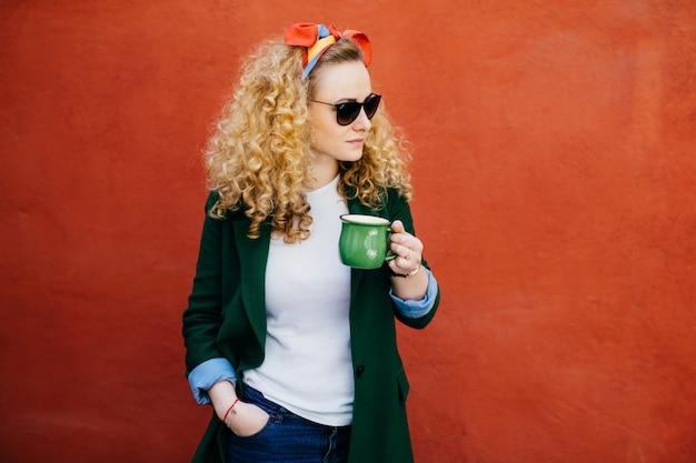 Porträt der hübschen frau mit tragendem stirnband des gelockten haares, stilvoller sonnenbrille und grüner jacke.