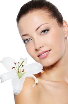 Porträt der hübschen gesunden frau mit lilie schließen ihr gesicht