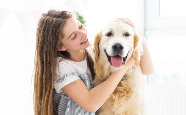Porträt der hübschen jugendlichen mit schönem hund zuhause