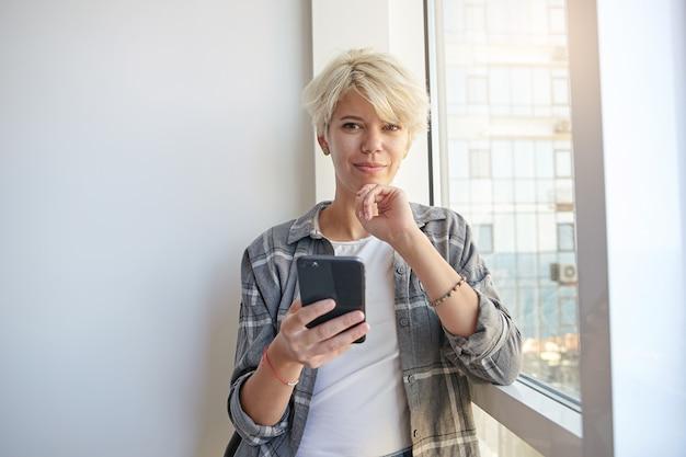 Porträt der hübschen jungen blonden frau mit kurzem haarschnitt, der über breitem fenster aufwirft, mit sanftem lächeln schaut und ihr kinn mit der hand berührt