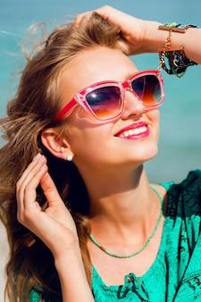 Porträt der hübschen jungen blonden schönen frau in der kühlen sonnenbrille, die auf dem sonnigen tropischen strand aufwirft