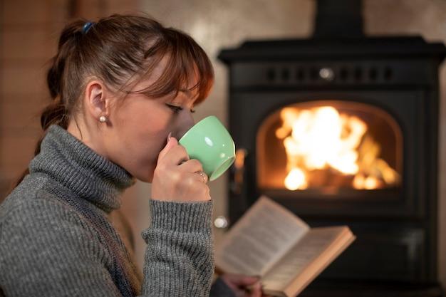 Porträt der hübschen jungen frau, die kaffee trinkt und buch nahe dem kamin liest