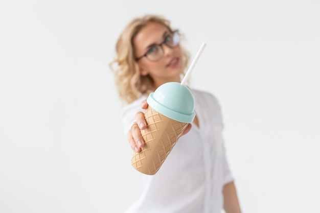 Porträt der hübschen jungen frau hält smoothie über weißer wand