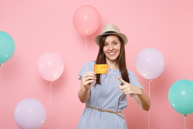 Porträt der hübschen jungen frau im blauen kleid des strohsommerhuts, das zeigefinger auf kreditkarte auf rosafarbenem hintergrund mit bunten luftballons hält. geburtstagsfeier-partyleute aufrichtige gefühle.