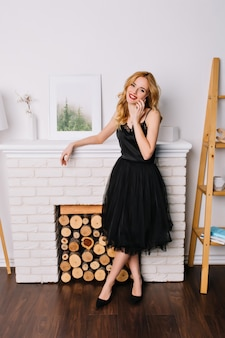 Porträt der hübschen jungen frau in voller länge, telefonisch sprechend und im zimmer mit schönem und modernem interieur lächelnd. trägt ein elegantes schwarzes kleid.