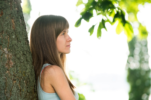 Porträt der hübschen jungen frau mit den langen haaren, die ordentlichen baumstamm im sommer stehen.
