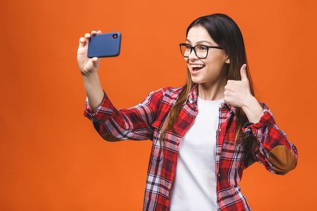 Porträt der hübschen jungen glücklichen frau, die selfie auf smartphone macht, lokalisiert gegen orange hintergrund. daumen hoch.