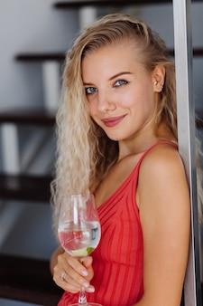 Porträt der hübschen jungen kaukasischen frau mit leichtem natürlichem make-up im roten minikleid