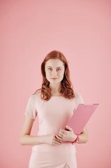 Porträt der hübschen jungen rothaarigen geschäftsfrau mit ordner, der gegen rosa hintergrund aufwirft