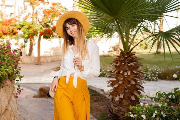 Porträt der hübschen kaukasischen frau im strohhut, in der weißen bluse und in der tasche des bali-stils, die im tropischen garten gehen.