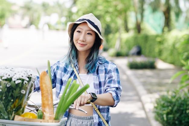 Porträt der hübschen lächelnden chinesischen jungen frau im eimerhut, der fahrrad draußen reitet