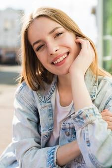 Porträt der hübschen lächelnden jungen frau, die kamera betrachtet