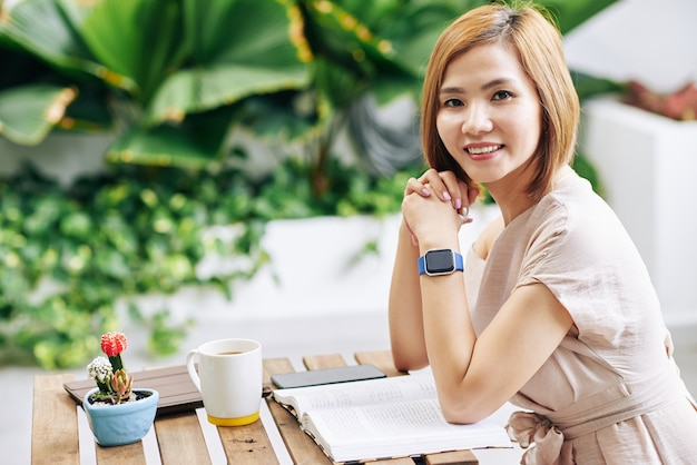 Porträt der hübschen lächelnden jungen vietnamesischen frau, die am kaffeetisch mit geöffnetem buch sitzt und kamera betrachtet