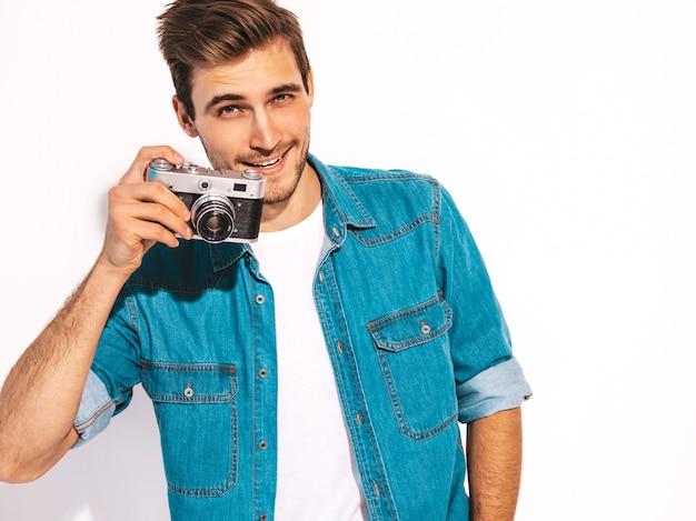 Porträt der hübschen lächelnden tragenden sommerjeans des mannes kleidet. vorbildlicher mann, der foto auf alter weinlesefotokamera macht.
