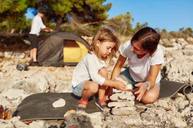 Porträt der hübschen mutter und des netten kleinen mädchens, die mit steinen spielt.