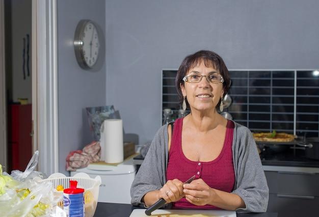 Porträt der hübschen reifen frau in der küche