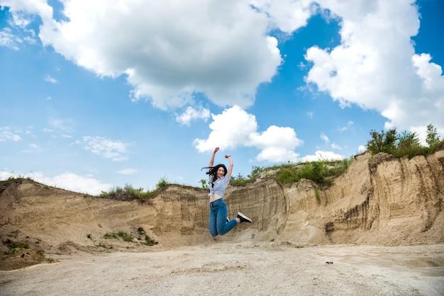 Porträt der hübschen schlanken frau, die vor sandsteinbruch, sommerlebensstil, freiheit steht