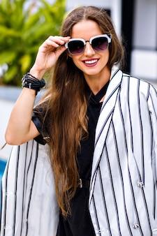 Porträt der hübschen stilvollen frau, die elegantes schwarzweiss-outfit trägt