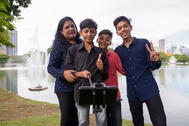Porträt der indischen familie, die zusammen am park entspannt