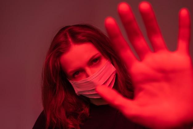 Porträt der infizierten jungen frau in der gesichtsmaske, die stoppgeste, rotlichteffekt macht