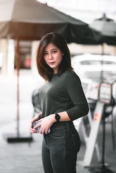 Porträt der intelligenten asiatischen frau, die vor coffeeshop am co-working space im einkaufszentrum am geschäftsviertelstandort lächelt. happy emotion relax concept