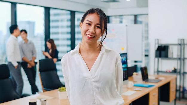 Porträt der intelligenten freizeitkleidung der erfolgreichen schönen geschäftsführerin, die kamera betrachtet und im modernen büroarbeitsplatz lächelt. junge asiatische dame, die im zeitgenössischen versammlungsraum steht.